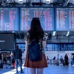 a woman looks at the departure boards at an airport